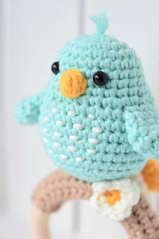 amigurumi bird on a wooden teething ring